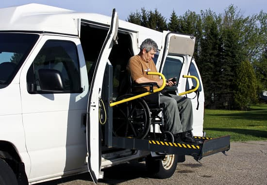 senior man in the wheelchair controlling ramp of van to exit