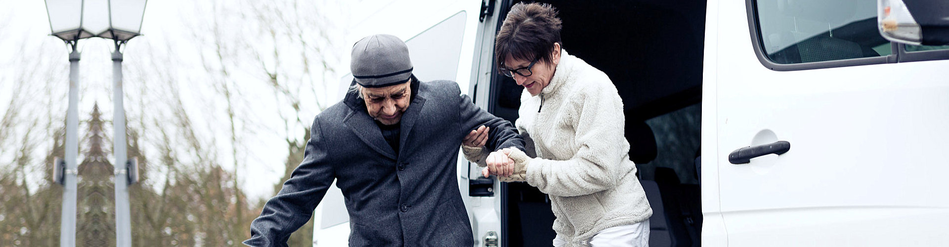 caregiver helping senior man to exit the van