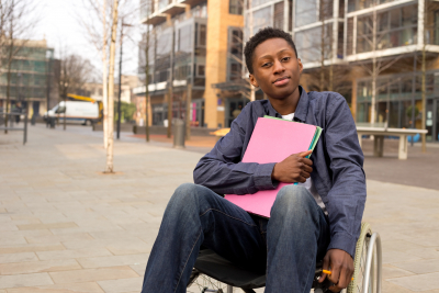 young student in a wheelchair holding folders
