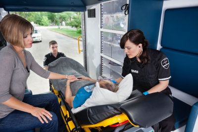 Ambulance workers caring for a senior woman with young caregiver