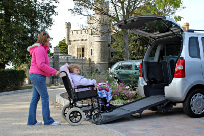 woman helping the senior woman on the wheelchair to get in the van